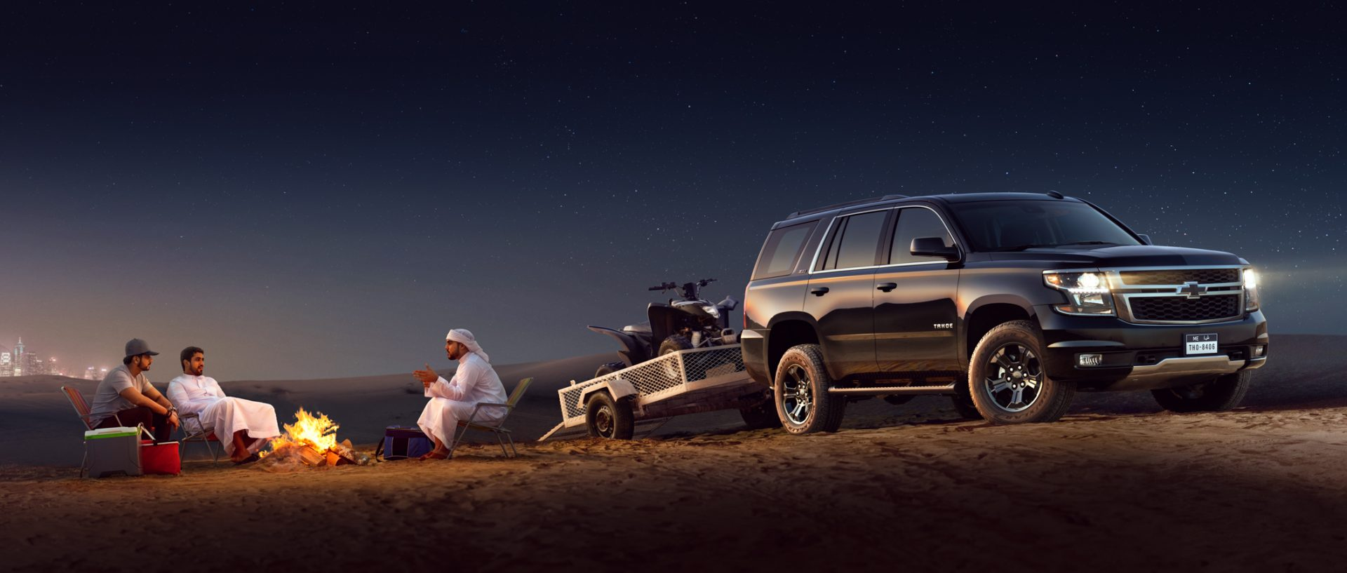 Chevrolet Tahoe, Midnight Edition. Photographed in the desert, next a camp fire and couple of friends sitting around it.