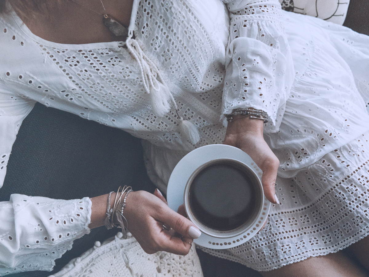 Top shot of a girl in a white dress holding a cup of black coffee. Beside her, a white pillow.